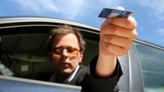 <p>man holding out credit card</p>